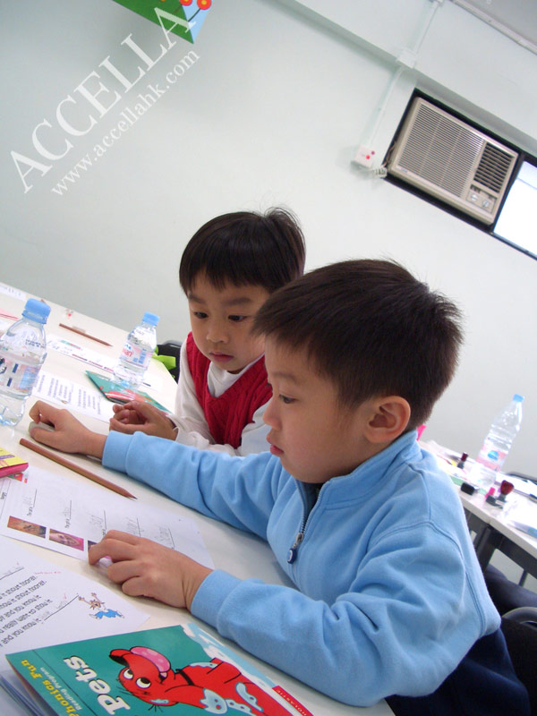 Alvin (foreground) and Henry learn how to describe different emotional states in English.
