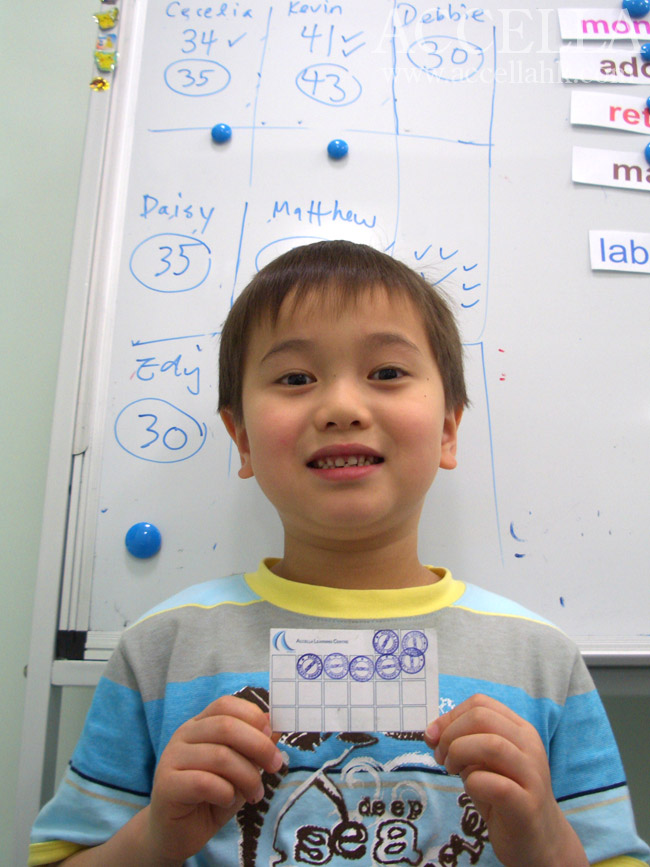 Kevin holding his Accella rewards card and standing in front of the points tally for last Saturday's P2 lesson.