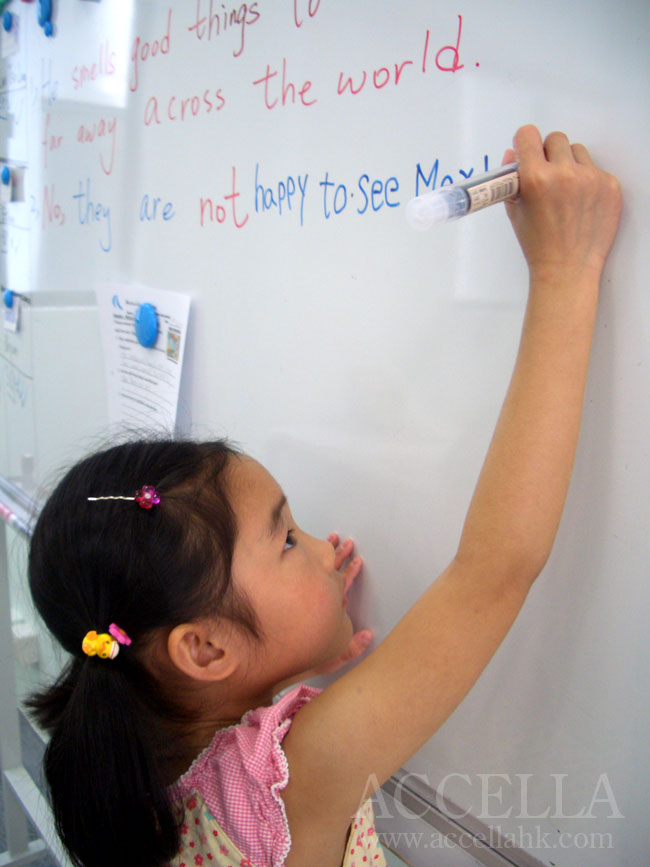 Jasmine writing one of her reading comprehension exercise answers on the whiteboard