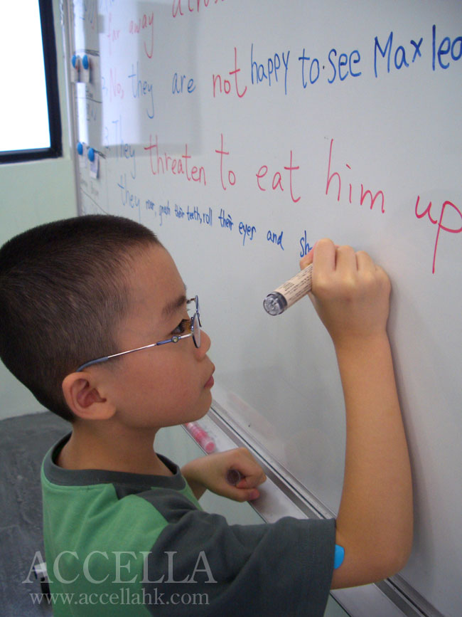 Bryan writing one of his reading comprehension exercise answers on the whiteboard