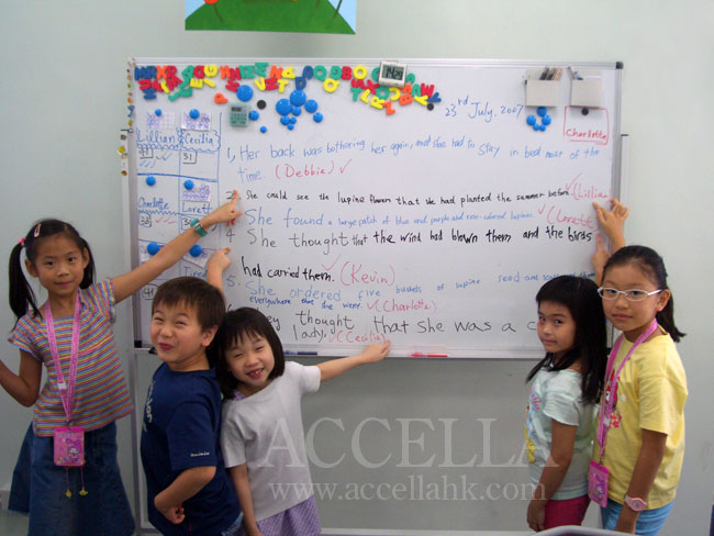 The students of one of our P3-P4 summer classes standing proudly in front of their reading comprehension exercise answers