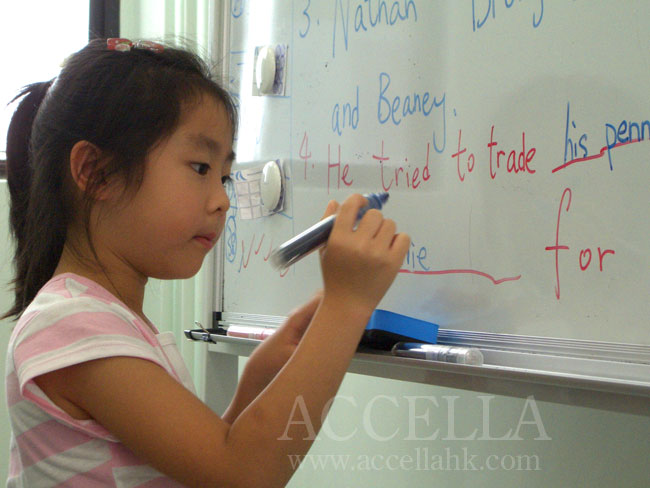 Anastasia writing one of her reading comprehension exercise answers on the whiteboard