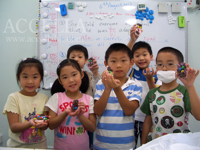 All of the students in one of our Summer Fun classes posing with their hand-crafted face biscuits.