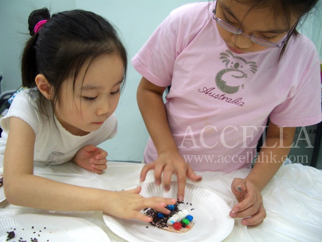 GwynethT and ShiraF working together to put the finishing touches on their creations.