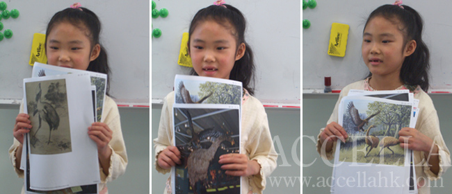 JasminL holding printouts of information that she looked up about 'Haast's Eagle and Terror birds' after sharing what she'd learned about both with her classmates.