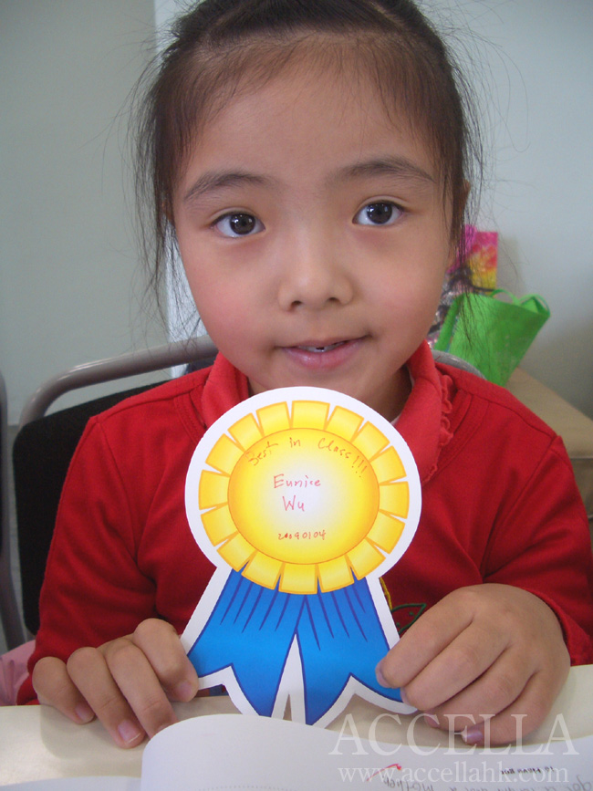 EuniceW displaying the ribbon that she got for accumulating the most points in last Sunday's class.