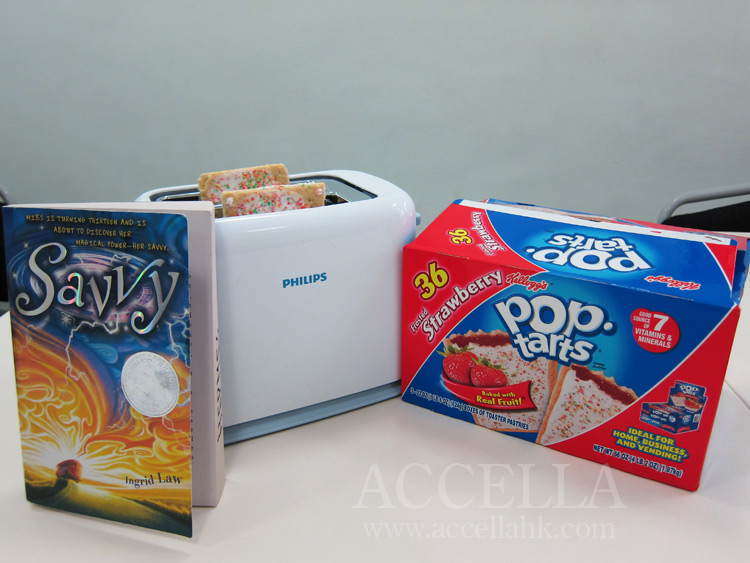 Left to right: paperback copy of savvy, toaster loaded with two strawberry Pop-Tarts, box of strawberry Pop-Tarts.